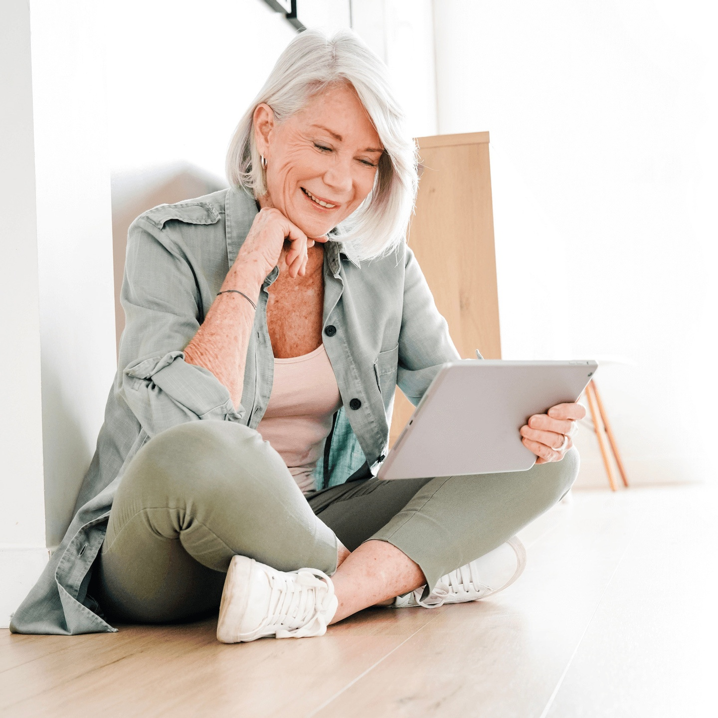 Photo of Woman Smiling While Looking at Tablet