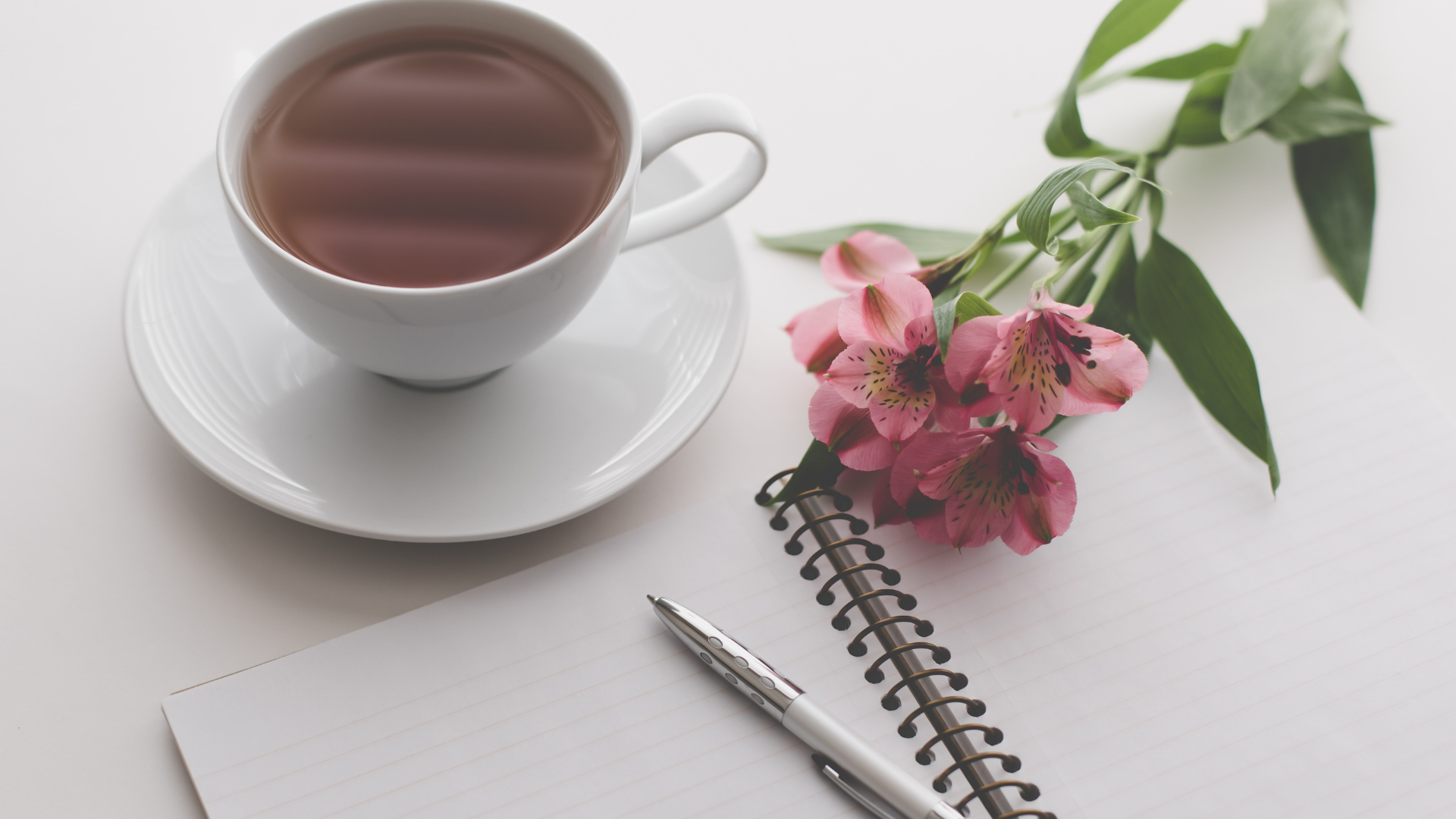 A photo of a desk with a notebook, pen and coffee.
