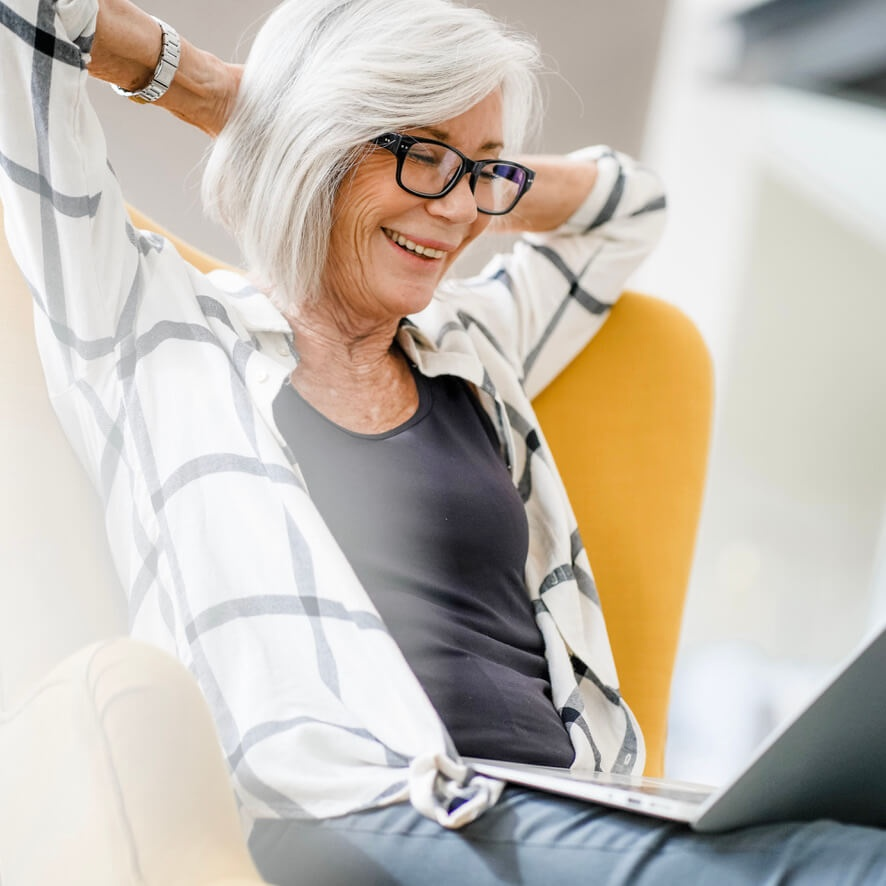 Photo of Woman Smiling Looking at Laptop Screen