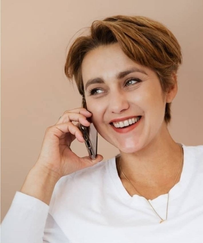 Young woman in white top smiling talking on cell phone