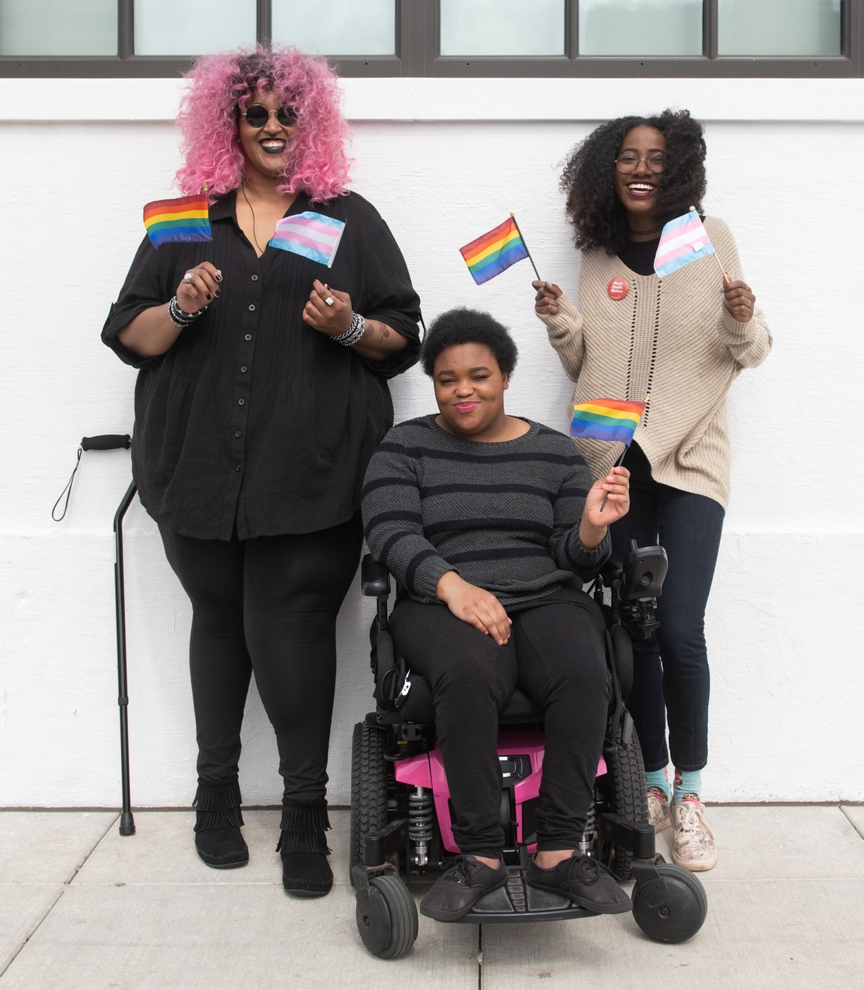 Three black people holding trans and gay flags. One has pink hair and a cane, one has a pink powerchair.