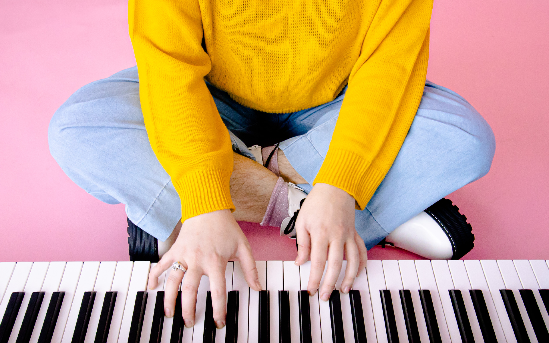 desktop wallpaper of a photo of a keyboard on a pink floor and hands with yellow sleeves playing it