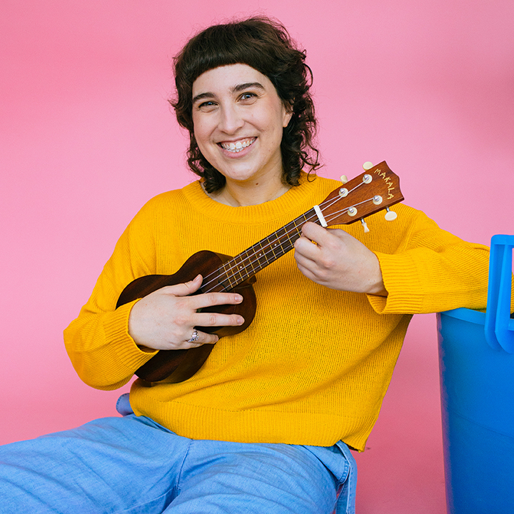 Portrait of Renée smiling and playing a ukuele