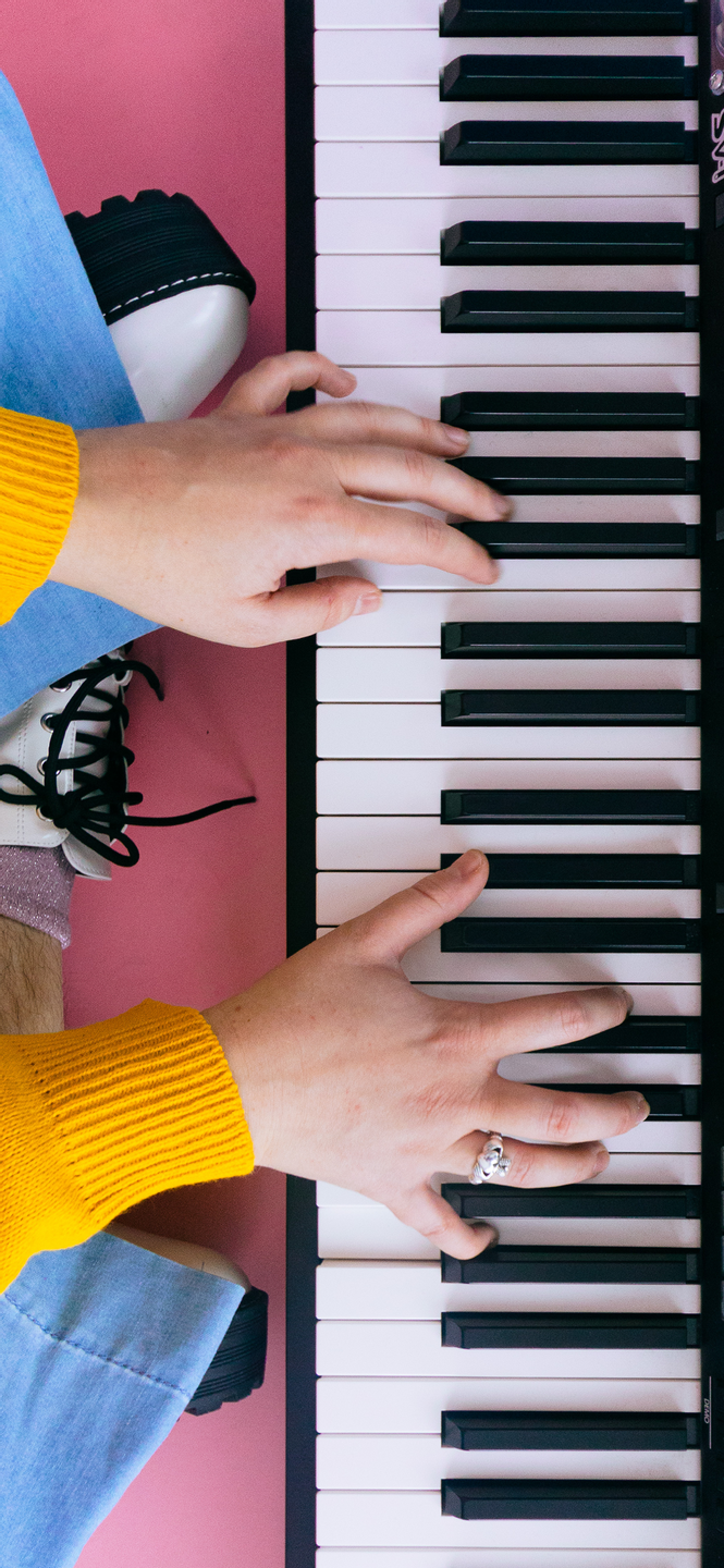 phone wallpaper of a photo of a keyboard on a pink floor and hands with yellow sleeves playing it