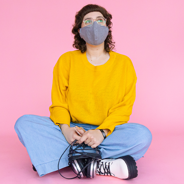 René sitting cross legged on a pink background wearing a cloth mask