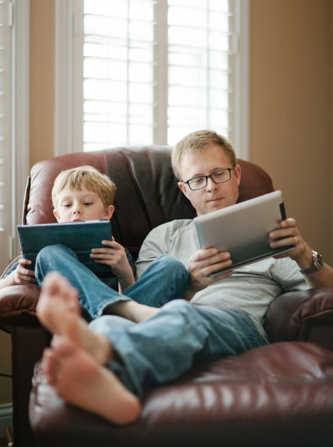 Father and child sharing a chair while both looking at their own mobile devices