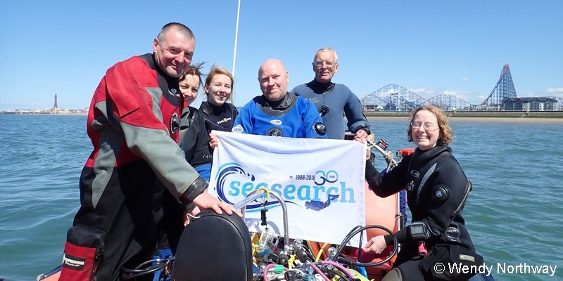Divers on a boat with a Seasearch flag