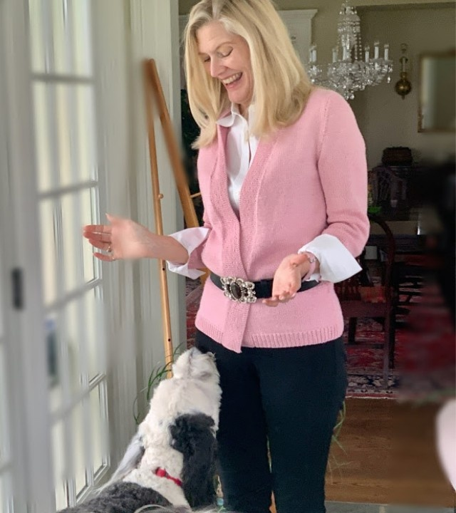 Blond woman (Ellen) wearing a pink handknit sweater smiling down at a dog that's looking up at her