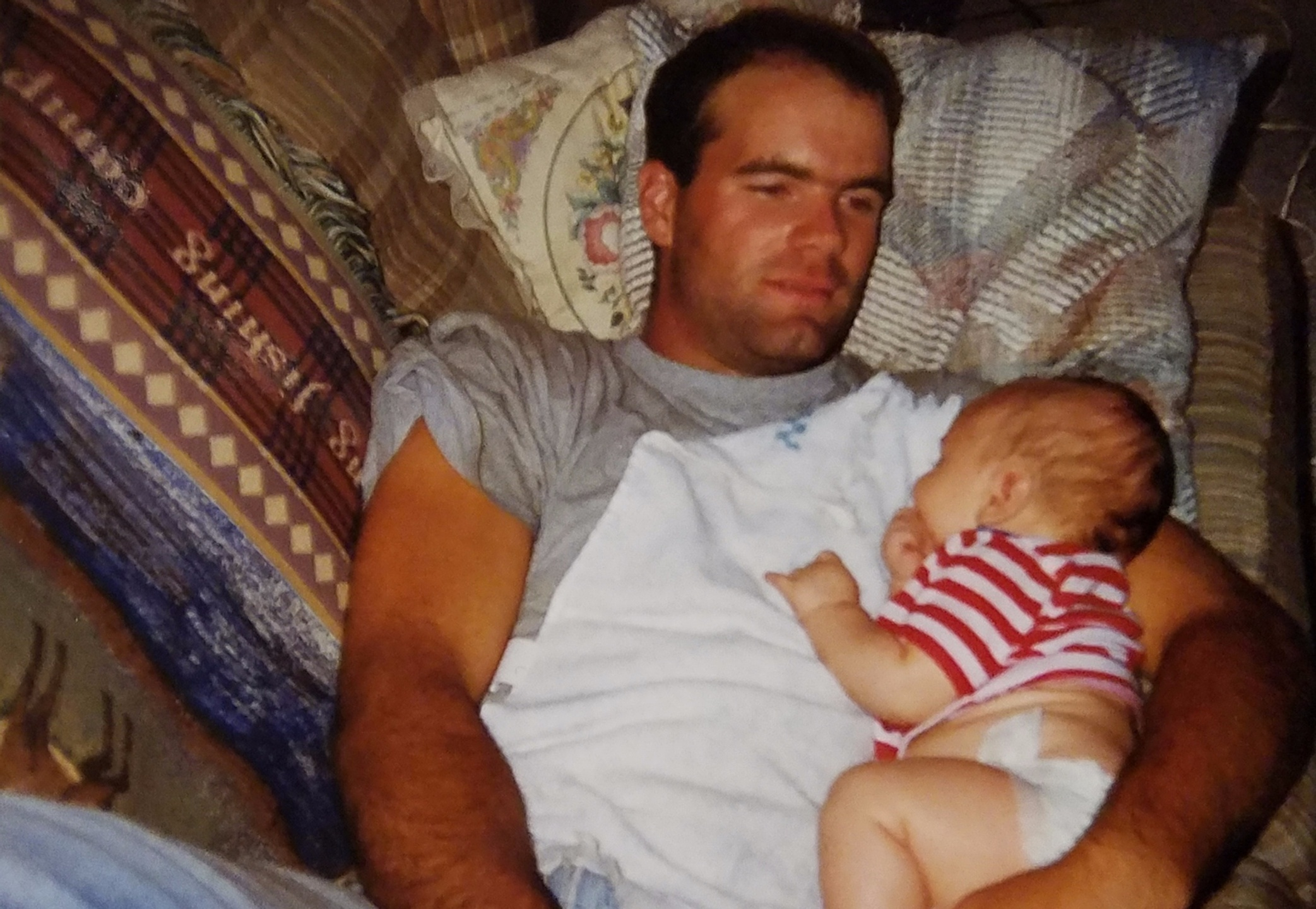 dad laying on couch holding infant