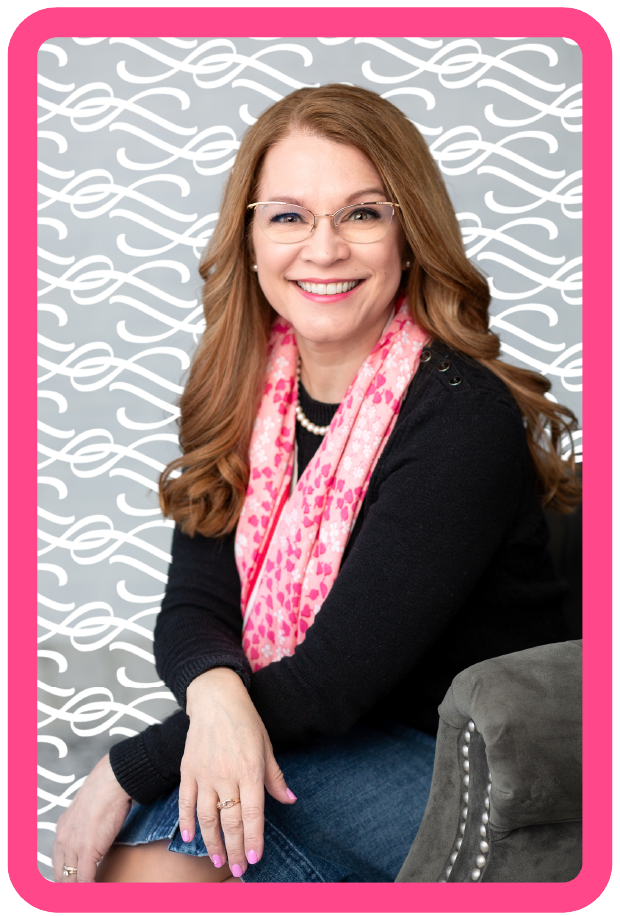 Headshot of Kelly Mann by Trayce Gregoire. Kelly is a middle-aged white women with thin silver glasses, pearls and light brown curled hair. She smiles at the camera with a pink scarf, black sweater, and jean skirt.