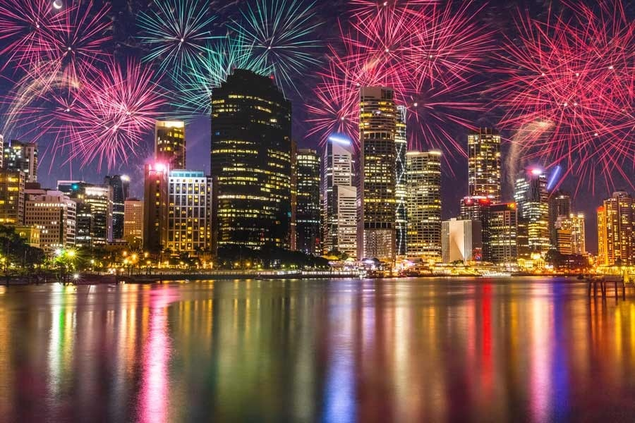 A photograph of a sky full of fireworks exploding over the city of Brisbane, reflected in the river
