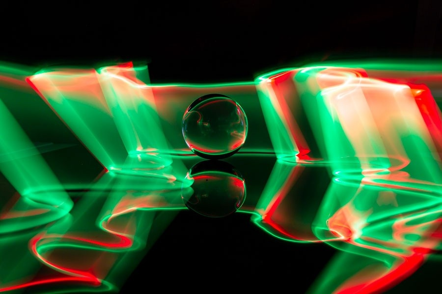 A glass ball (lensball) with light painted streaks reflecting on a black background