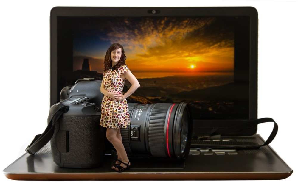A photograph of a miniature girl standing in front of a camera and laptop