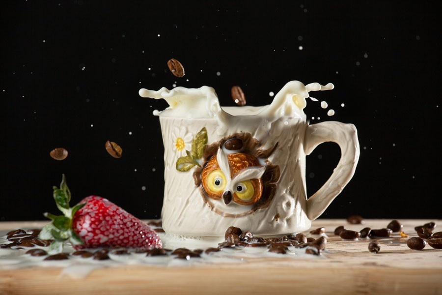 A product photo of coffee falling into an owl mug with splashing milk