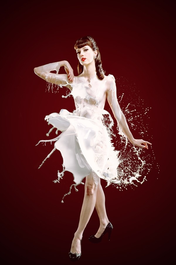A photograph of a retro styled girl wearing a dress made of milk splashes