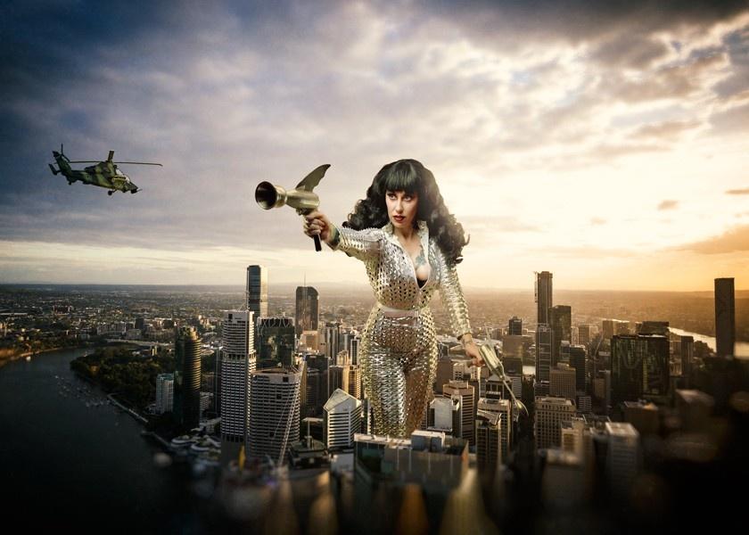 A composite photograph of a giant alien girl walking through a cityscape