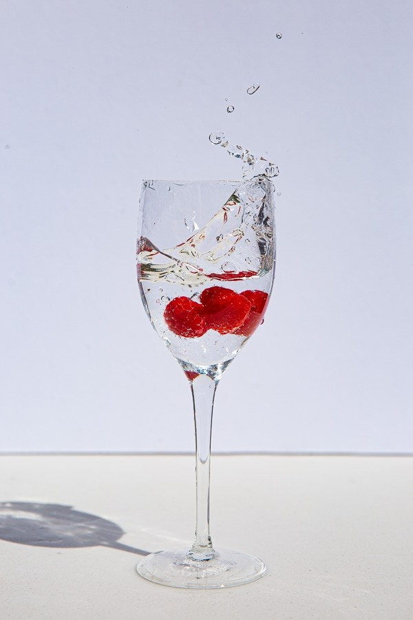 A photograph of raspberries splashing into a wine glass full of water