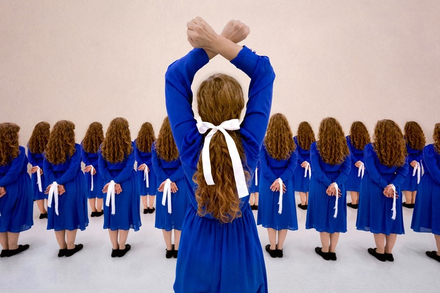 A photograph of a girl standing in defiance while her clones are bound