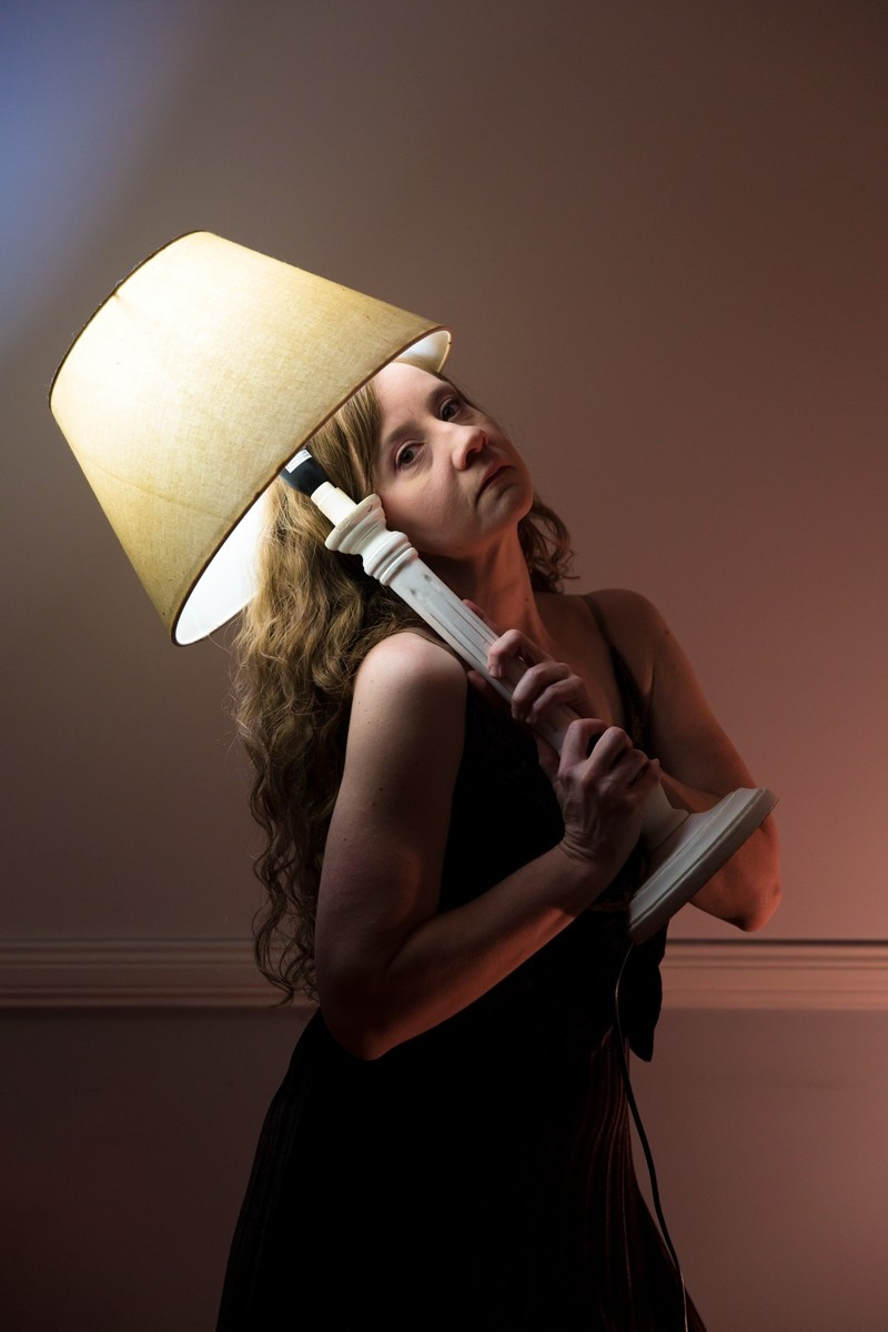 A photograph of a girl with a lamp shade on her head, lit by the lamp
