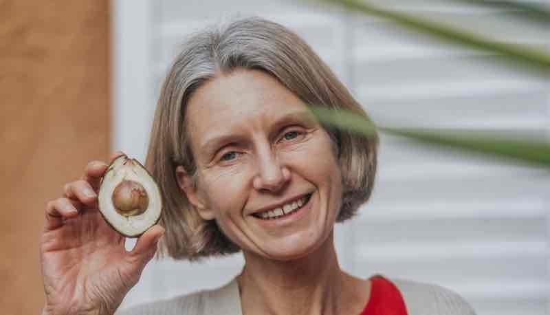 Dr Orlena holding a large lettuce, healthy vegetable.