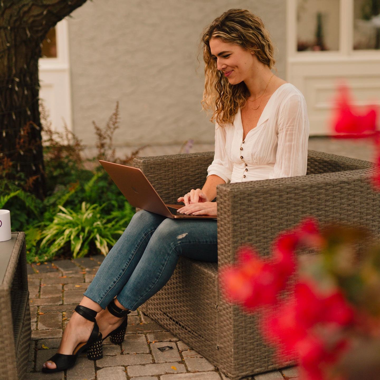 Ava Beilke working on a laptop outside