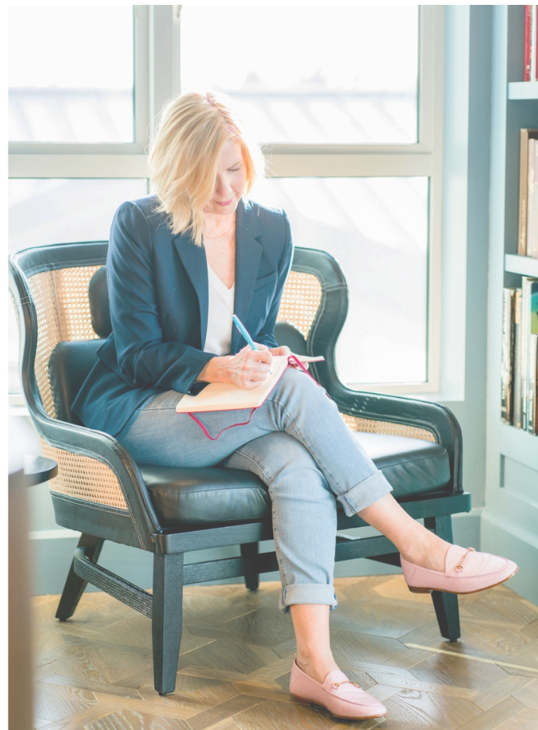 Blonde woman in navy jacket sitting in writing in a journal.
