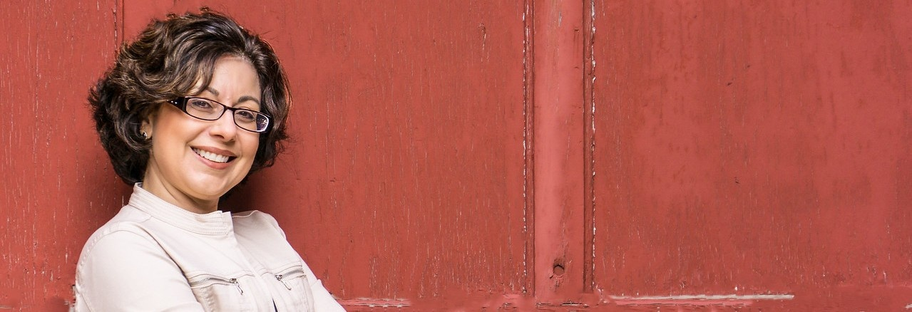 Julie standing in front of a red barn door with her arms folded