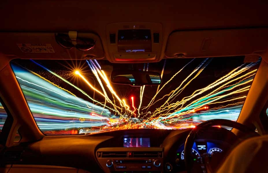 A photograph of light trails through the windscreen of a moving car
