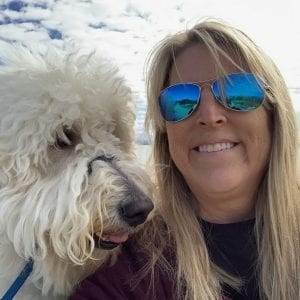 Very cool-looking  blonde woman wearing sunglasses smiles and poses for a photo with her white, poofy dog who is looking at her adoringly. Snow in the background.