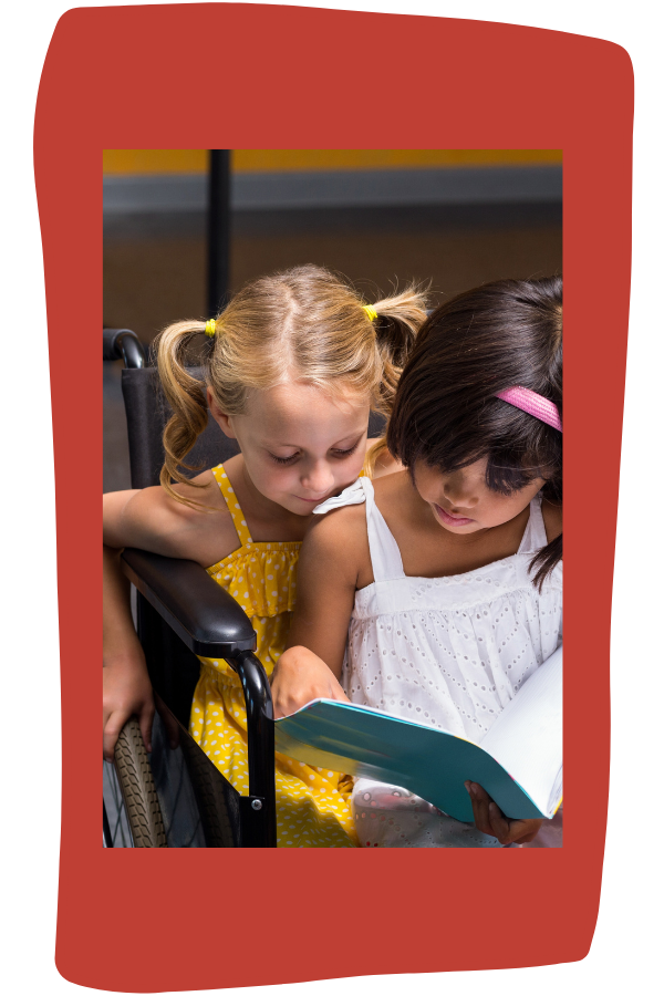 Girls sitting in wheelchair reading book together. Blonde girl with pig tails is on bottom. Brown-haired girl with pink headband  sits in her lap holding the open book.
