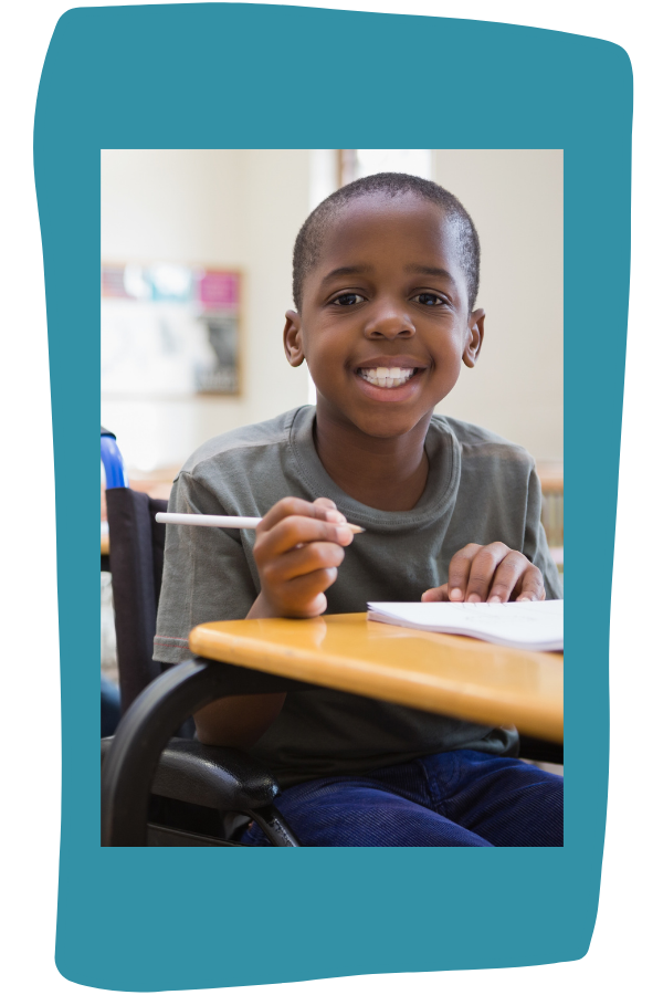 Disabled pupil smiling at camera in classroom. Boy is Black with short hair, and wearing gray t-shirt, holding pencil.