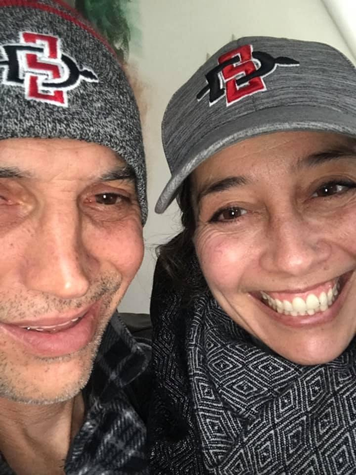 Joaquin Carson, a handsome Latino wearing an SDSU beanie, smiles next to his sister, Diana, who is wearing an SDSU baseball cap and has a beaming smile on her face.