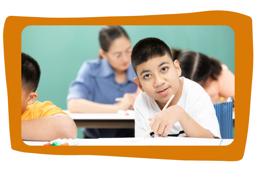 Child with a disability works on his own in classroom. He is writing at desk, looking at camera. He is Asian, is holding a pencil, and wears a white t-shirt. Teacher in background is helping other students.