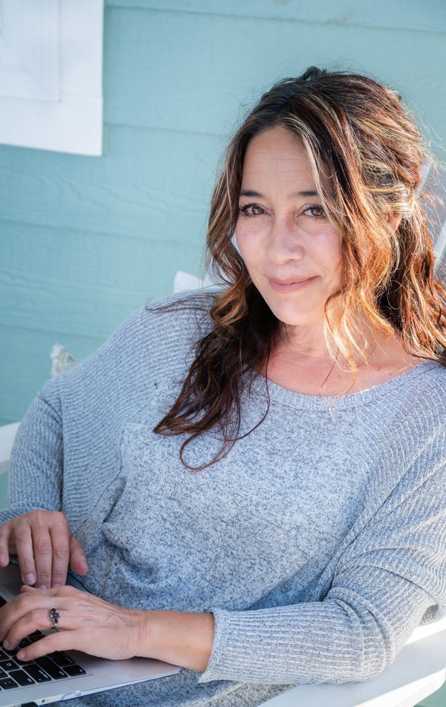 Diana Pastora Carson, a Latina woman, sits in a sunlit porch, with laptop in her lap, looking over toward the camera. Long brown hair is pulled back with some draped to front over her shoulder. She is wearing a grey sweater. Blue building in background.
