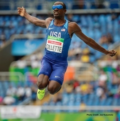 Lex Gillette, Paralympic Athlete, mid-air during triple long jump. People in stands in stadium in background.