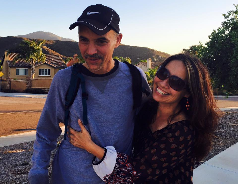 Joaquin and Diana Carson, siblings embrace as they pose for a picture during a walk. Joaquin is wearing a baseball cap and sweatshirt with his backpack. Diana wears a flowy blouse and dark sunglasses. Both are smiling.