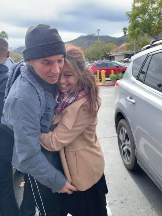 Joaquin and Diana Carson, siblings, stand in a parking lot, both wearing coats. Joaquin is wearing a beanie. Diana is hugging him tightly and smiling.