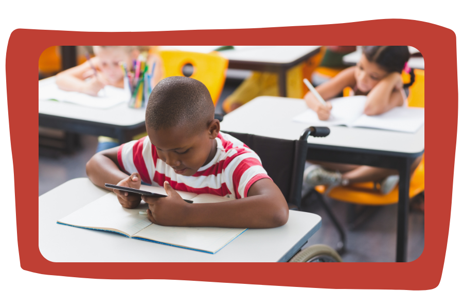 Disabled schoolboy using digital tablet. He is Black with short hair, and wearing a red and white striped shirt. Other children in background sitting at their desks, working.