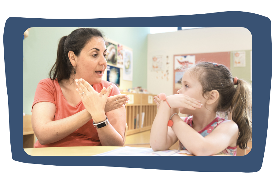 Teacher in classroom sits with a student and is using American Sign Language to communicate with or teach her student. Teacher has long brown hair pulled back into a ponytail. Student has blonde hair in a ponytail and is paying close attention to the teacher.