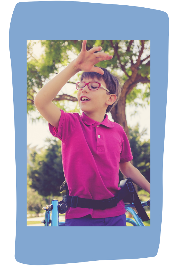Boy with dark hair uses a walker and smiles as his arms are in motion as he walks.