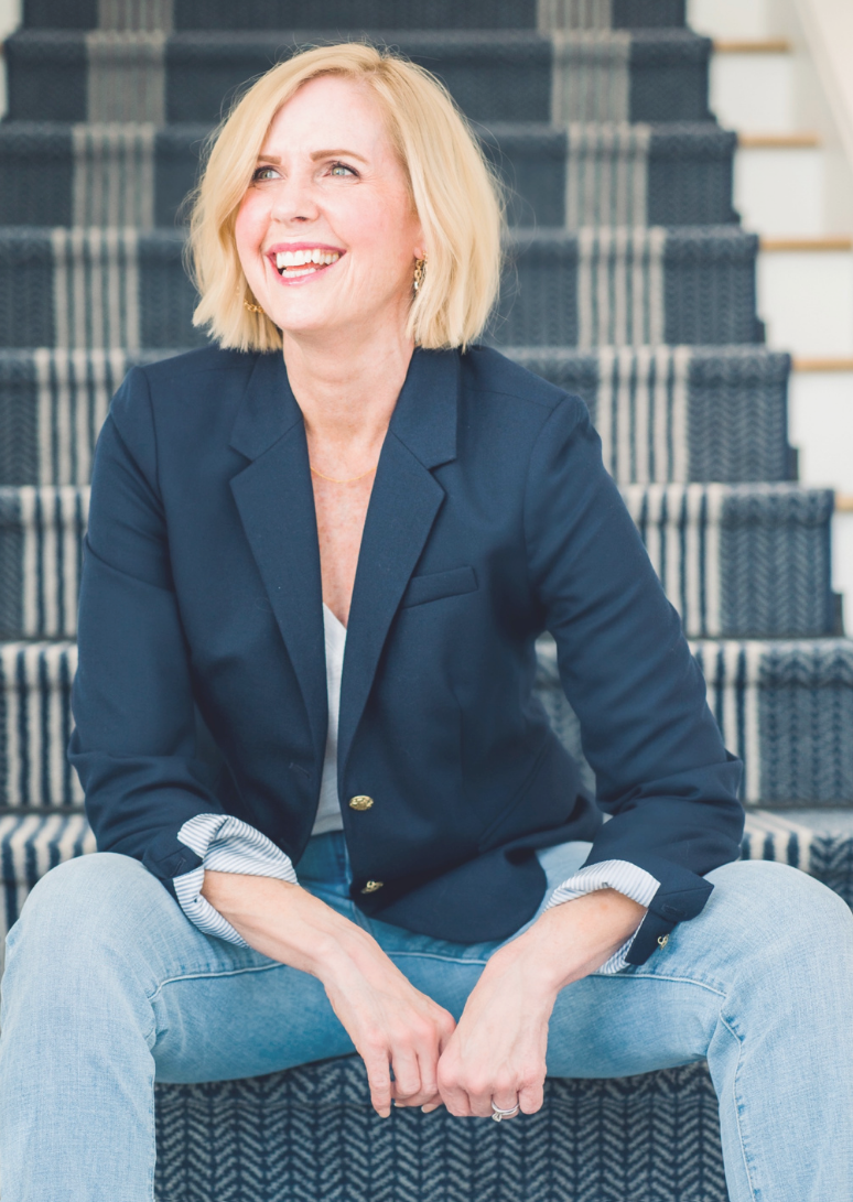blonde woman sitting on stairs smiling