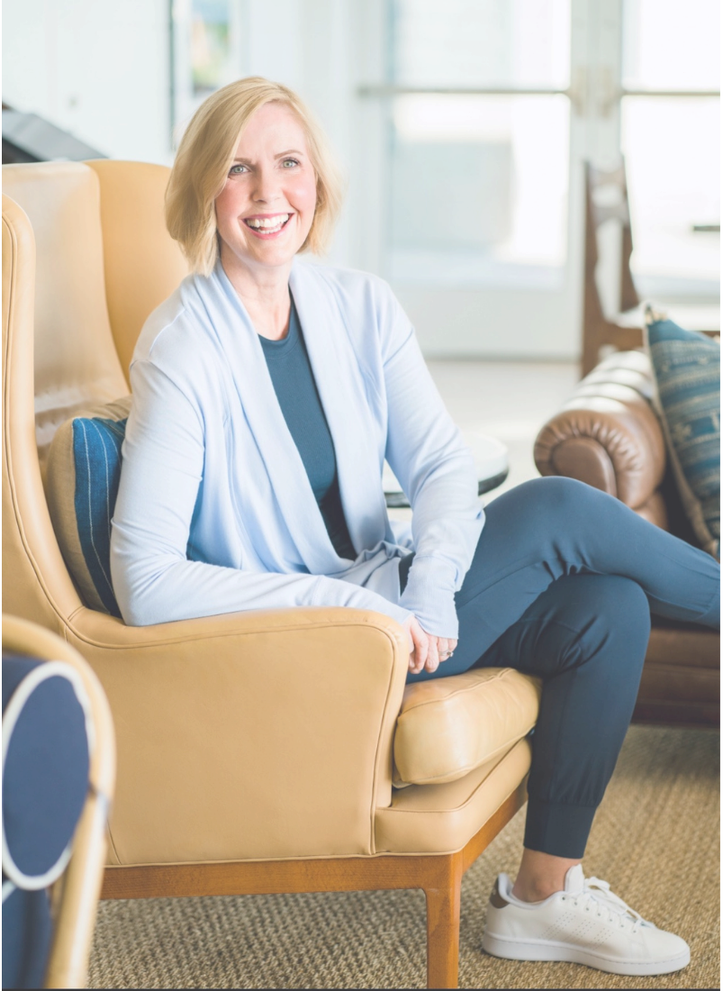 Woman sitting in brown leather chair smiling looking at camera.