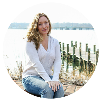 Jeanette Sealy is looking at the camera with a soft smile. She is sitting by water with a dock behind her wearing a white sweater and jeans.