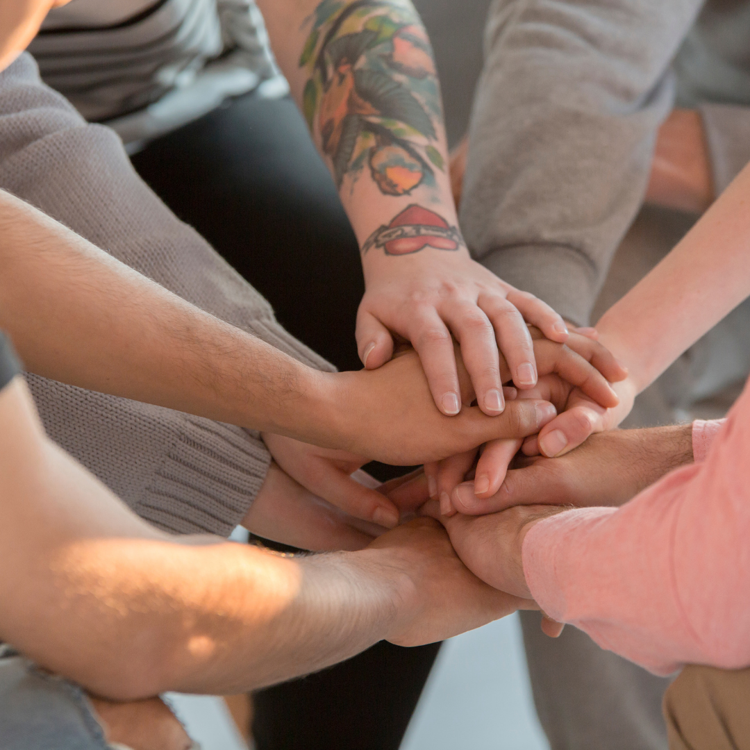 a group of Yoga teachers holding hands