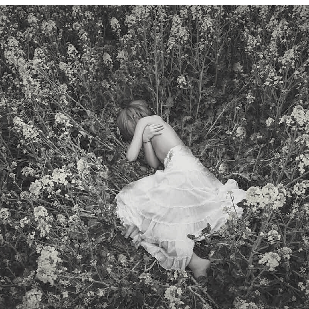a woman lying in a field of flowers. She is hugging herself and wearing a long skirt.