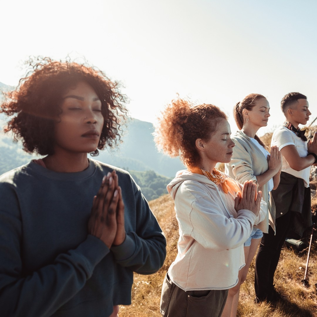 How to host a Yoga retreat. A group of women with hands in prayer on a mountain.