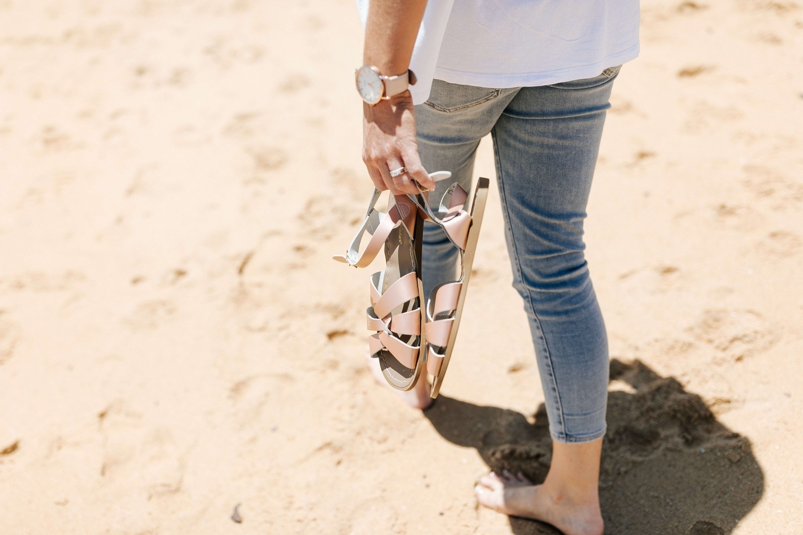 Dr Emily Amos from MORE THAN MILK walking on the beach with shoes in hand