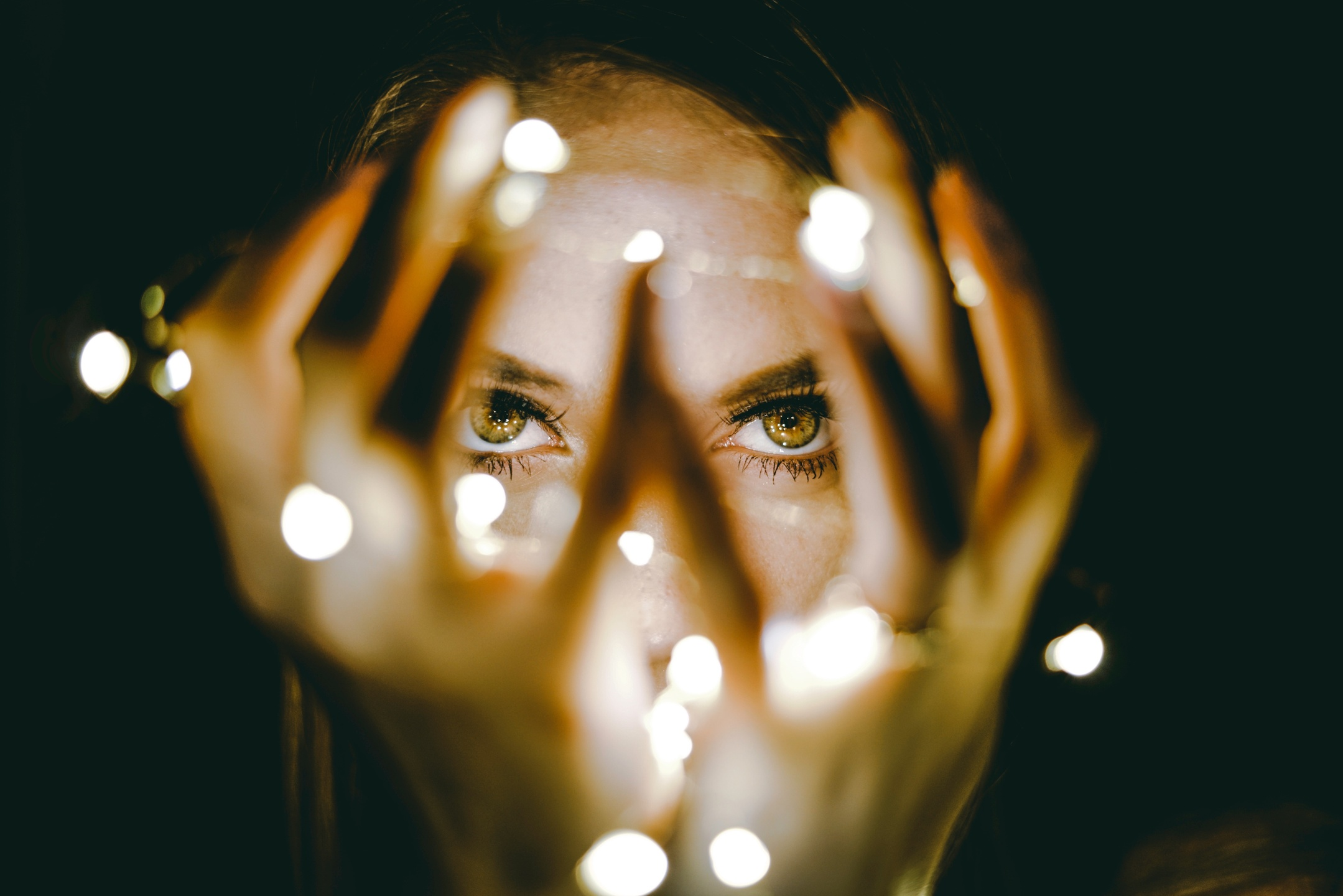 image shows woman holding blurred twinkle lights in front of her face with eyes in focus
