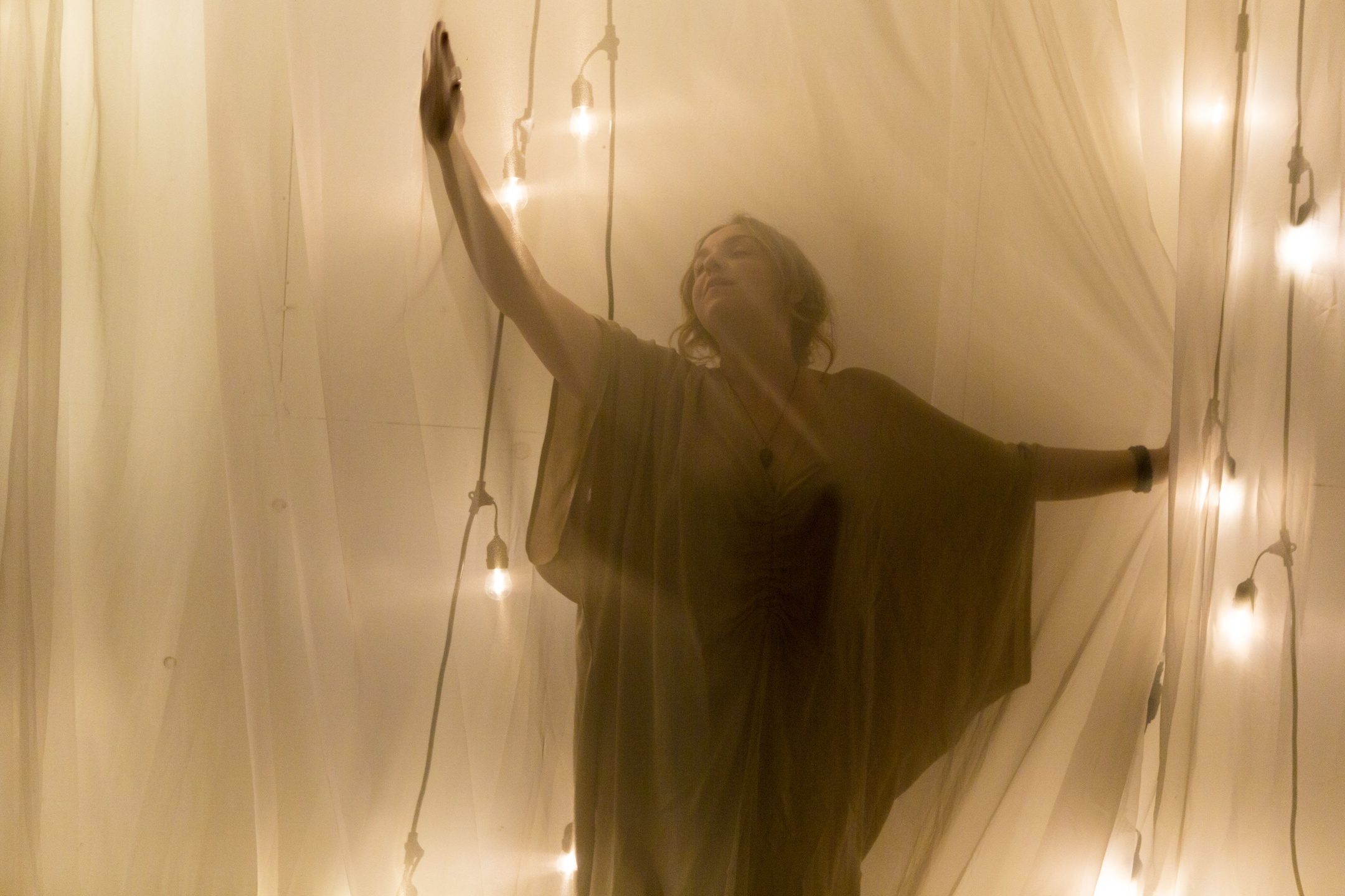 image shows woman with arms stretched behind sheer fabric with twinkle lights