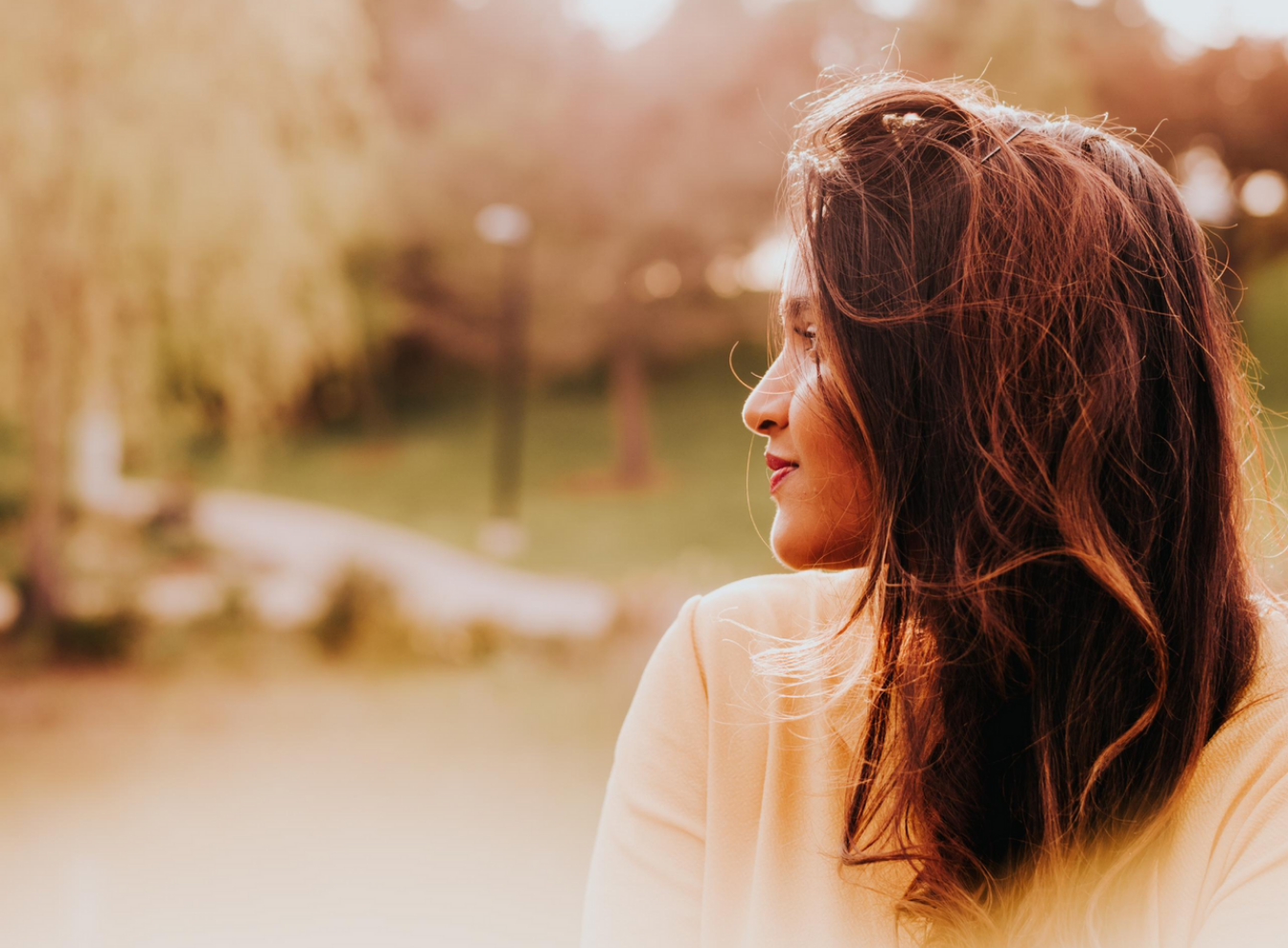 Image of Jenny, a South Asian woman staring off into the distance at a park.